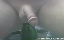 Hunk sits on a bottle and measures his cock